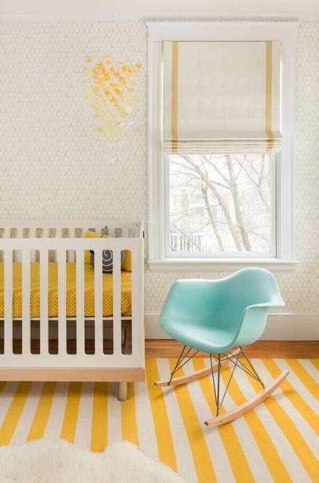 46. Quarto de bebê amarelo e branco decorado com cadeira de balanço verde água e tapete listrado – Foto: Mandarina Studio