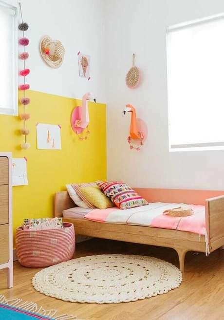 52. Quarto de menina amarelo decorado com tapete redondo de crochê e cama de madeira – Foto: Pinterest