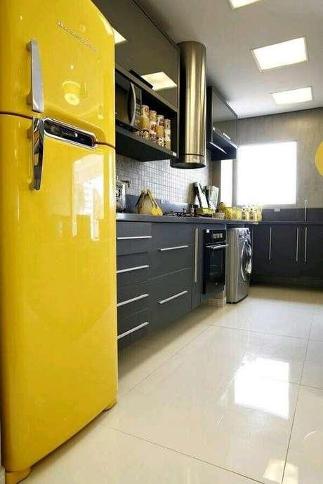 16. Decoração com armários planejados pretos e geladeira amarela para cozinha integrada com lavanderia – Foto: Webcomunica