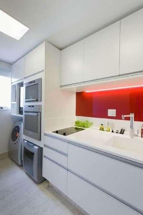 33. O revestimento vermelho colocou um toque personalizado na cozinha com lavanderia toda branca – Foto: Vazlon Brasil