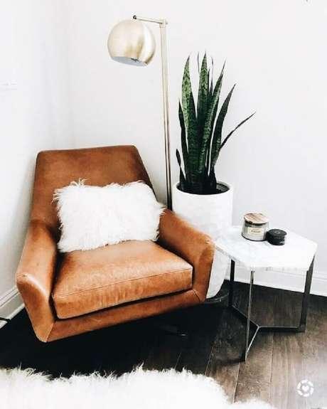 12. Decoração com estilo hygge com vaso de plantas e poltrona de couro com pequena almofada branca – Foto: Pinterest