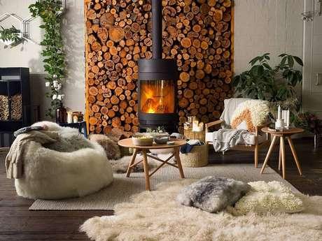 20. Decoração hygge para sala de estar ampla com lareira, puffa com tapete de pelos e parede com lenhas – Foto: Secret Roomz