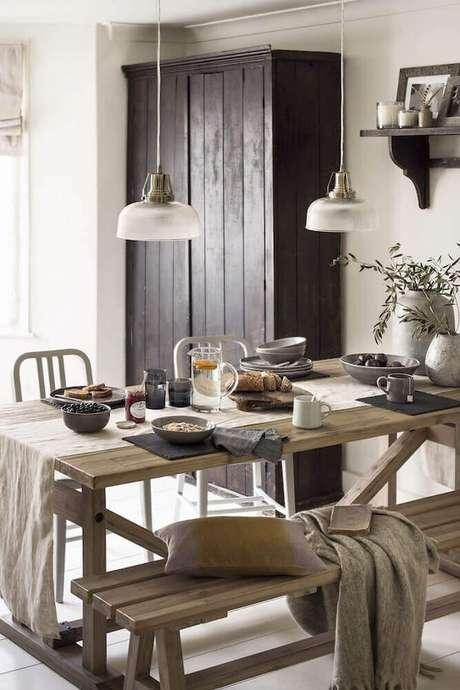23. Hygge decor para sala de jantar com estilo rústico com mesa de madeira, mantas e pendentes sobre a mesa – Foto: Culture Trip