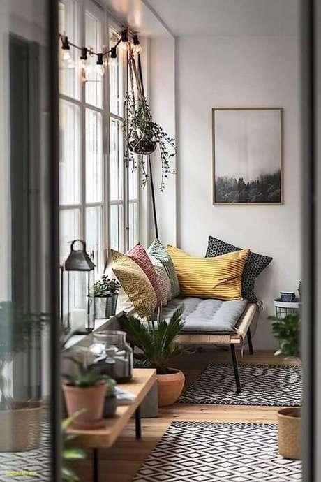 24. Decoração com estilo dinamarquês com varal de lâmpadas, tapete com estampa geométrica, vasos de plantas e mutias almofadas – Foto: Fontana