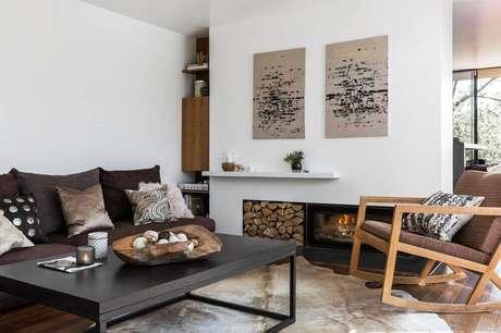 30. Estilo hygge para sala de estar com lareira, mesa de centro preta e cadeira de balanço de madeira – Foto Amara