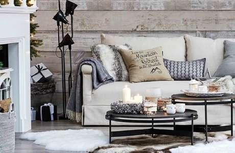 36. Decoração hygge para sala de estar com parede revestida de madeira, muitas almofadas com manta sobre o sofá e luminária preta – Foto: Deco Therapy