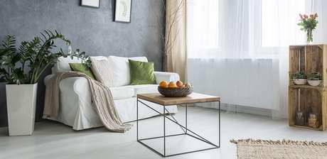 41. Sala de estar minimalista decorada com estilo dinamarquês com vasos de plantas, detalhes em madeira e ambiente com bastante iluminação natural – Foto: Soferia