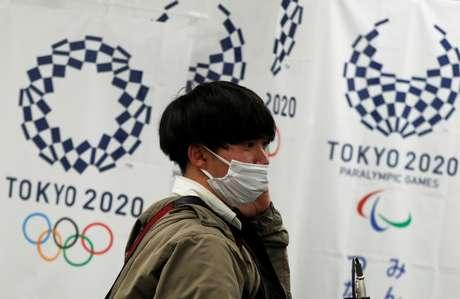 Homem com máscara de proteção em frente à logomarca dos Jogos Tóquio 2020 17/03/2020 REUTERS/Issei Kato