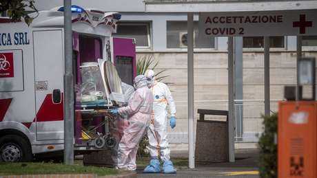 Equipe médica coleta um paciente de uma ambulância na Itália