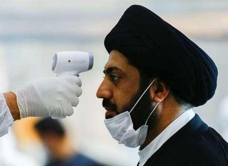 Membro de equipe médica checa temperatura de clérigo em meio a preocupações com aumento de infecções por coronavírus no Irã 15/03/2020 REUTERS/Alaa al-marjan