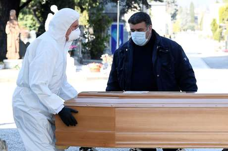 Homens com máscara e roupa de proteção transportam caixão para cemitério em Bergamo 16/03/2020 REUTERS/Flavio Lo Scalzo