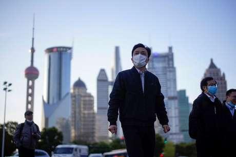 Pessoas com máscara de proteção no centro financeiro de Xangai 19/03/2020 REUTERS/Aly Song