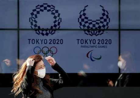 Mulher com máscara de proteção contra coronavírus caminha em frente a painel com a logo dos Jogo de Tóquio 19/03/2020 REUTERS/Issei Kato