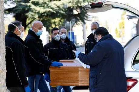 Homens com máscaras de protenção pegam caixam de pessoa morta pelo coronavírus em cemitério em Bérgamo, na Itália 16/03/2020 REUTERS/Flavio Lo Scalzo