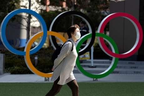 Mulher com máscara de proteção passa por anéis olímpicos em Tóquio 13/03/2020 REUTERS/Athit Perawongmetha