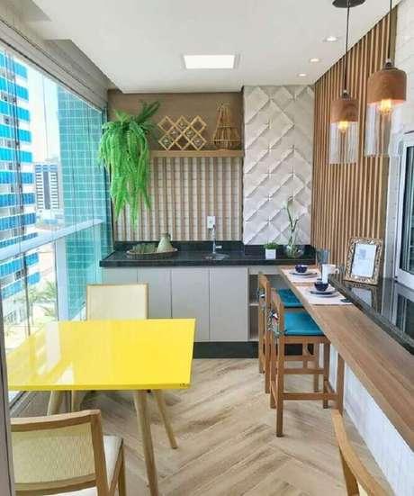 12. Apartamento com área gourmet pequena e simples decorada com mesa amarela e banqueta azul – Foto: Dicas de Mulher
