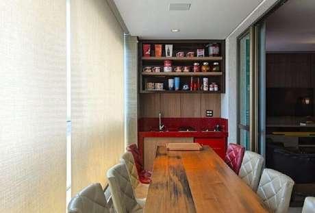 13. Apartamento com área gourmet pequena e simples planejada com bancada vermelha e mesa de madeira – Foto: Mariana Borges e Thaysa Godoy