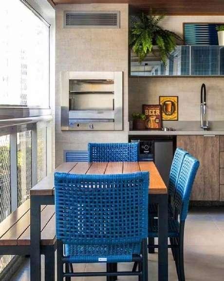 29. Cadeiras azuis e mesa de madeira para decoração de área gourmet pequena com churrasqueira – Foto: Pinterest