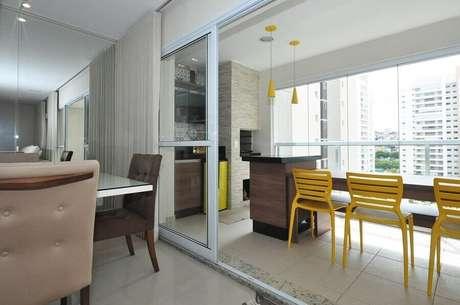 36. Área gourmet pequena de apartamento decorada com cadeiras e pendentes amarelos – Foto: Condecorar Arquitetura e Interiores