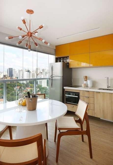 45. Decoração moderna com lustre arrojado para área gourmet pequena com móveis planejados de apartamento – Foto: Oliveira Arquitetura