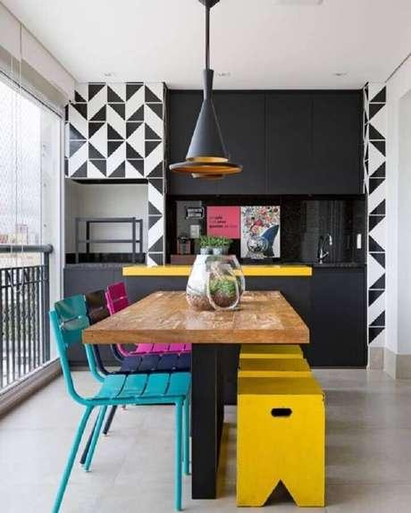 52. Cadeiras coloridas para decoração de área gourmet pequena planejada com móveis pretos – Foto: Easy Deco