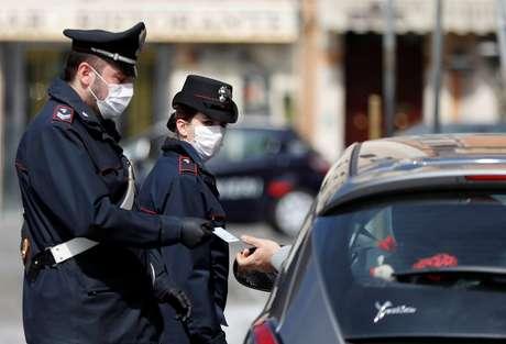Policiais italianos usam máscara de proteção enquanto verificam se motorista tem razão válida para viajar durante bloqueio no país 21/03/2020 REUTERS/Yara Nardi