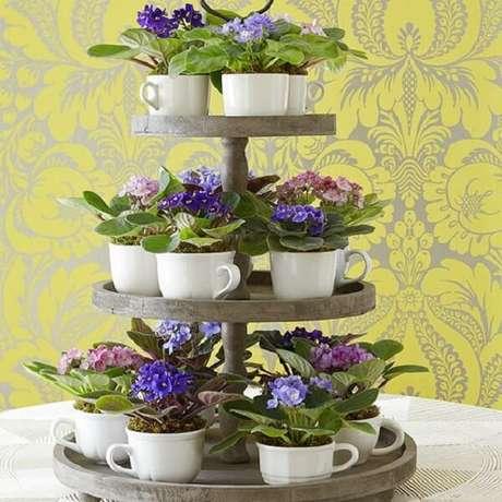23- O arranjo para evento utiliza mudas de violetas plantadas em xícaras brancas. Fonte: Jeito de Casa