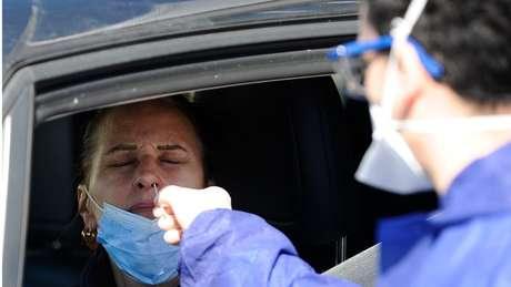 Agente sanitário coleta amostra de motorista na França para testar presença do novo coronavírus