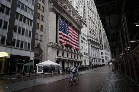 Homem passa de bicicleta em frente à Bolsa de Nova York, EUA 23/03/2020 REUTERS/Mike Segar