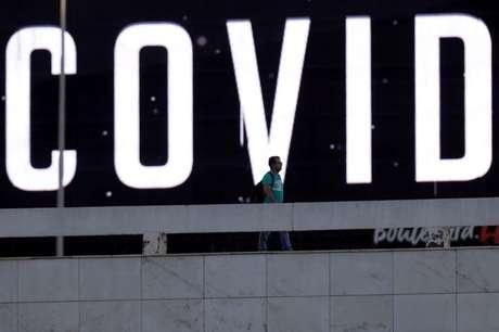 Homem passa em frente a outdoor de LED em meio a surto da doença do coronavírus (Covid-19), em Brasília 24/03/2020 REUTERS/Ueslei Marcelino
