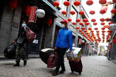 Pessoas usando máscaras de proteção caminham em distrito histórico de Pequim 26/03/2020 REUTERS/Thomas Peter