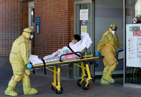 Profissionais de saúde transferem paciente de ambulância para hospital em Leganés, na Espanha 26/03/2020 REUTERS/Susana Vera