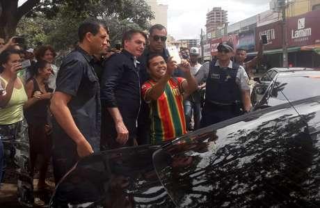 O presidente Jair Bolsonaro é assediado por apoiadores ao visitar vários comércios locais ainda abertos em Brasília, na manhã deste domingo, 29 de março de 2020. Bolsonaro saiu por volta de 9h30 do Palácio da Alvorada e seguiu para um posto de gasolina. Ele desceu do carro para cumprimentar e tirar fotos com frentistas que estavam trabalhando.