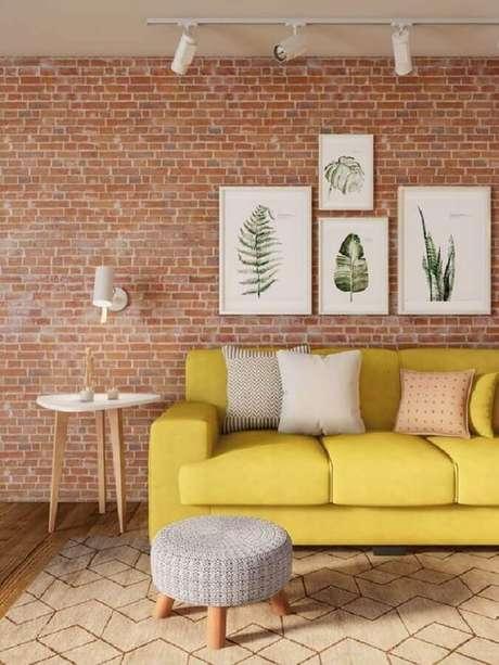 2. A parede de tijolo a vista deu um toque acolhedor na decoração da sala amarela com quadros brancos – Foto: Dcore Você