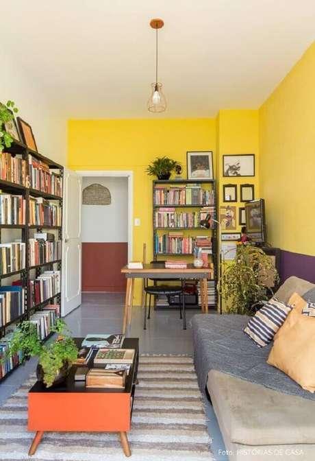 13. Decoração para sala com parede amarela com estante para livros e tapete listrado em cores neutras – Foto: Histórias de Casa