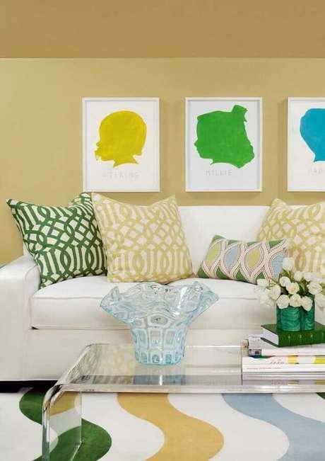 14. Decoração para sala amarela com sofá branco e tapete e almofadas coloridas – Foto: Houzz