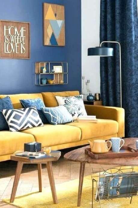 9. Decoração de sala azul e amarela com mesa de centro de madeira – Foto: Archzine