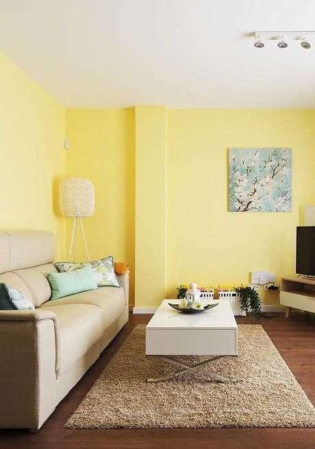 22. Sala com parede amarela decorada com mesa de centro branca – Foto: Webcomunica
