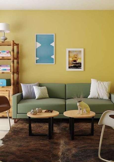 23. Decoração para sala com parede amarela com sofá verde claro e mesa de centro redonda – Foto: Architecture Art Designs