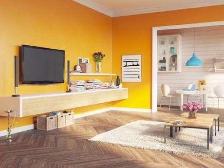 25. Decoração simples para sala com parede amarela e rack suspenso – Foto: Istock