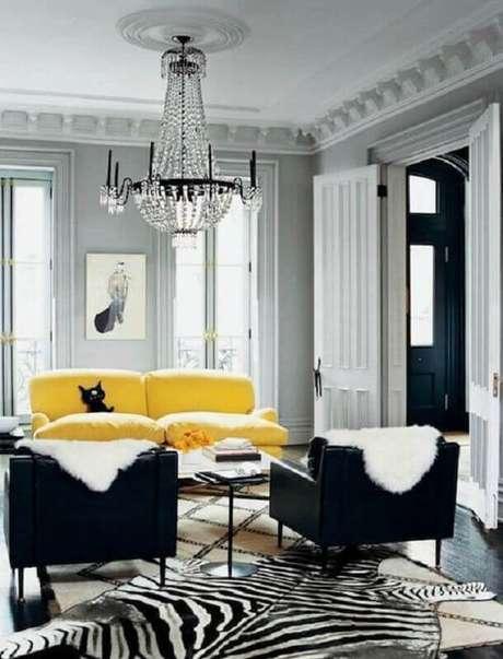 26. Decoração sofisticada com lustre de cristal para sala cinza e amarelo com poltronas pretas – Foto: Encadreé Posters