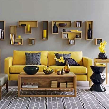 5. Decoração de sala cinza e amarela com nichos diferentes e mesa de centro de madeira – Foto: Dcore Você