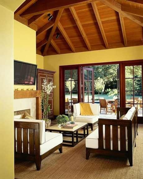 8. Combine móveis de madeira e tons de marrom para a decoração rústica de sala com parede amarela – Foto: Decoratorist