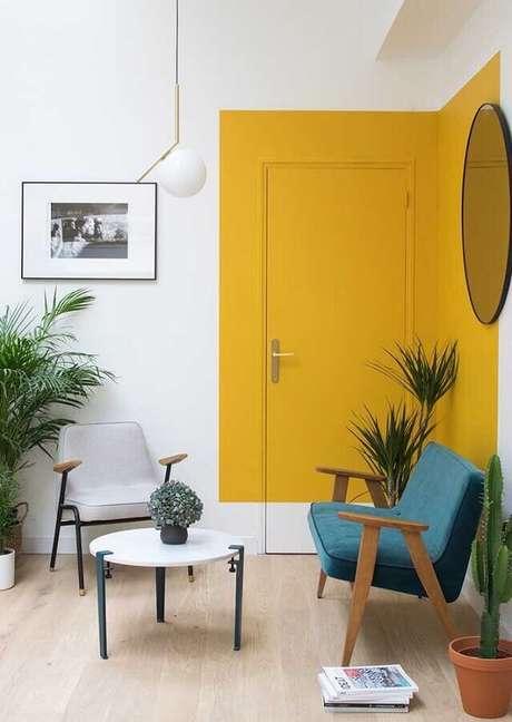 29. Poltrona de madeira para decoração de sala amarela com espelho redondo – Foto: Homedit