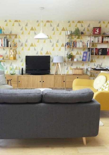 31. Poltrona para sala amarela decorada com sofá cinza e papel de parede com estampa geométrica – Foto: Histórias de Casa
