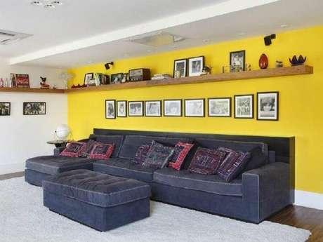 32. Decoração simples com prateleira de madeira e sofá cinza para sala com parede amarela – Foto: Ricardo Lopes