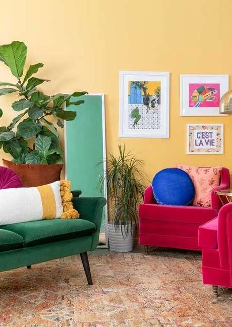 40. Sala amarela decorada com poltronas rosa e sofá verde – Foto: Pinterest