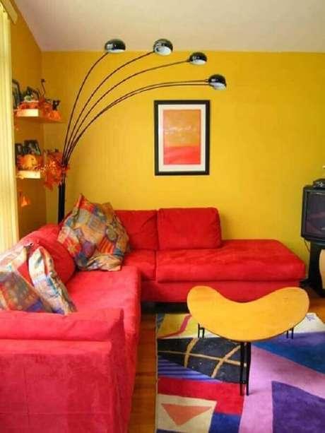 7. Decoração para sala amarela com sofá de canto vermelho e almofadas coloridas – Foto: Pinterest