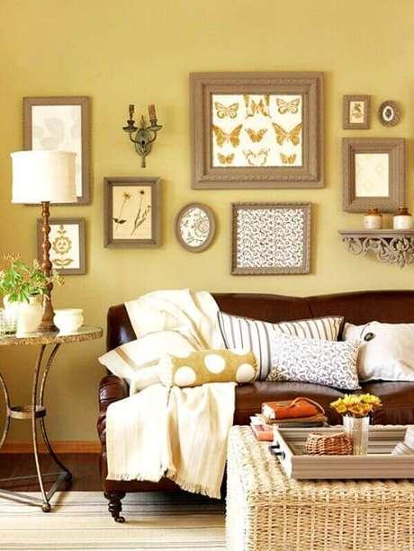 41. Sala amarela decorada com sofá de couro e várias almofadas em cores neutras – Foto: Pinterest