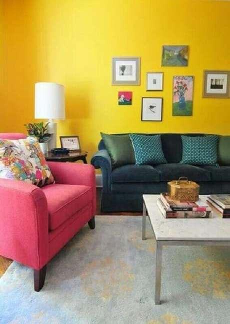 46. Sala com parede amarela decorada com poltrona cor de rosa e sofá azul escuro – Foto: Pinterest